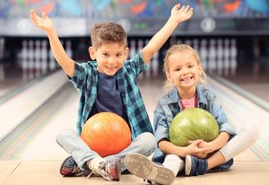 kids-sitting-with-bowling-balls
