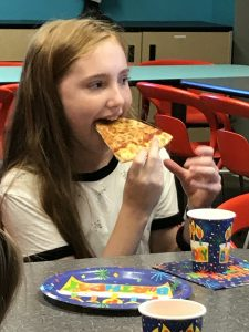 girl-eating-pizza-at-party